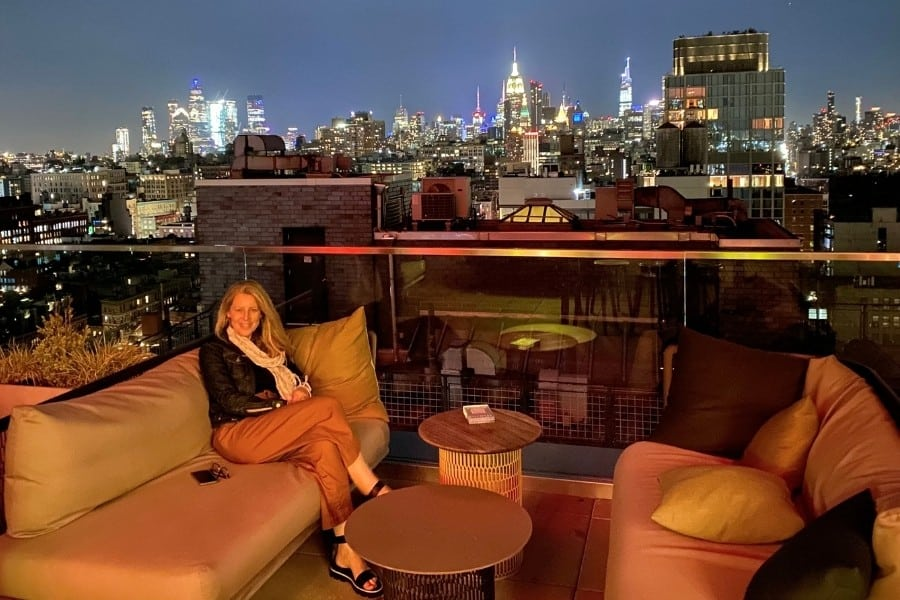 Susan Heinrich sits on a rooftop lounge in New York City withe the city and buildings beyond