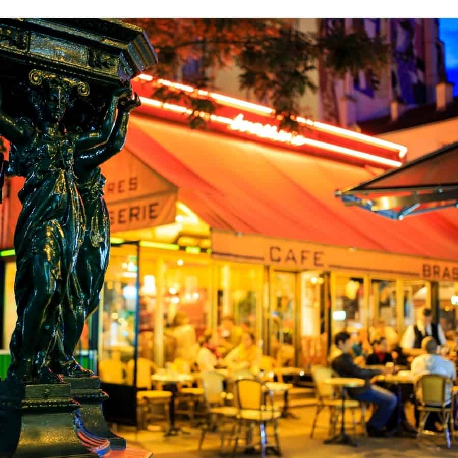 A Paris café with a traditional awning is lit up. People sit at outdoor tables, a popular thing to do in Paris at night.