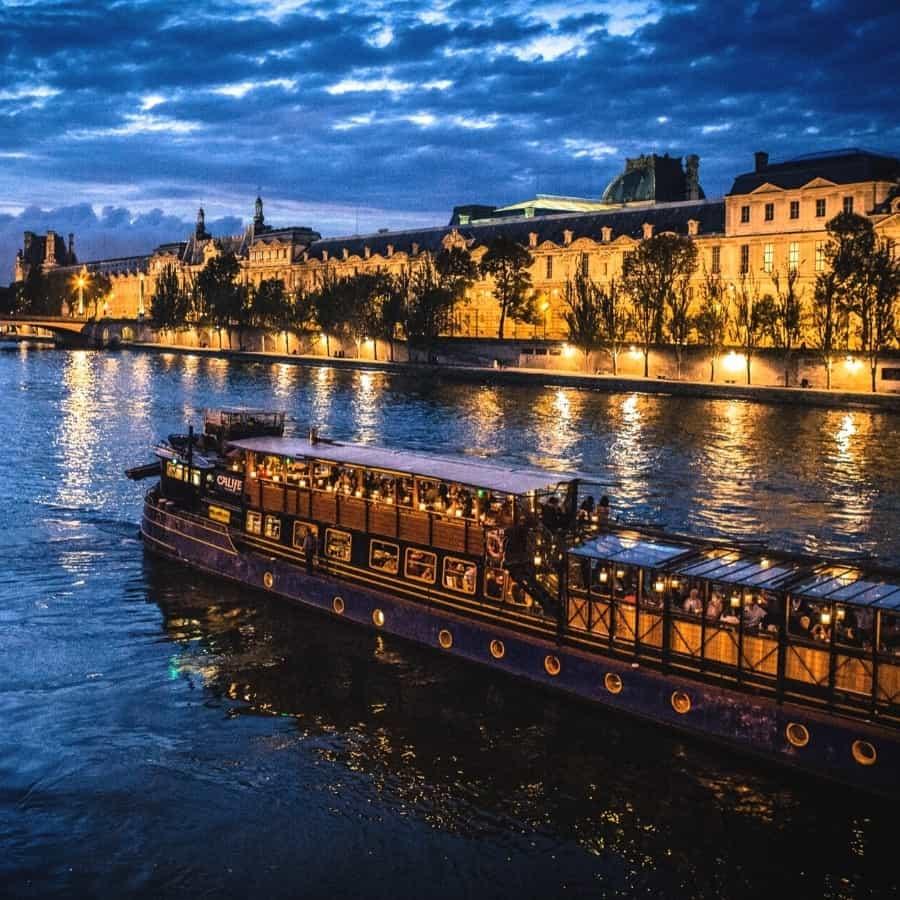 A boat travels along Paris's Seine River at night, with buildings lit up next to the river