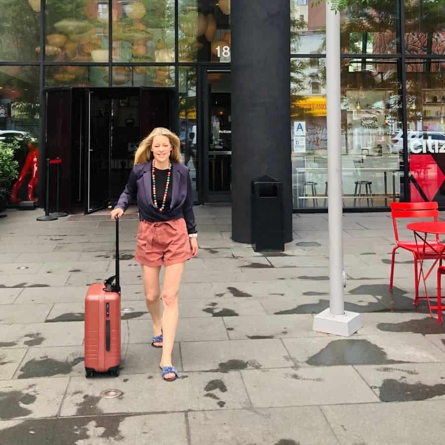 Susan Heinrich walks away from the CitizenM Bowery hotel with her Monos carry-on luggage