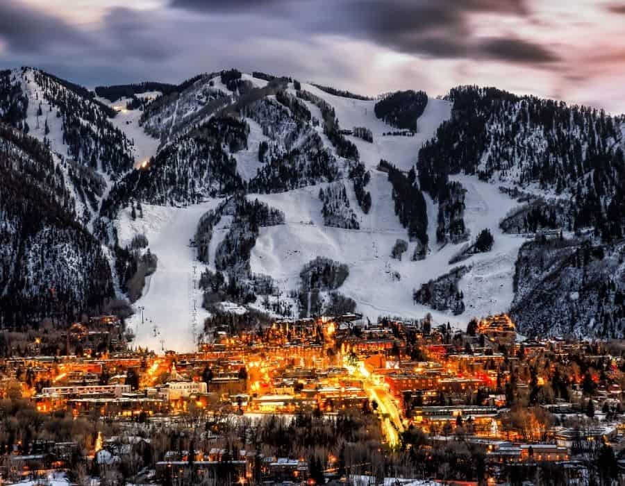 The town of Aspen Colorado at night with Aspen ski hill beyond, a dream girls trip destination