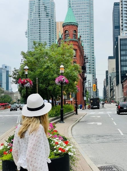 Susan Heinrich stands looking at Toronto's flatiron building, the Gooderham building completed in 1892