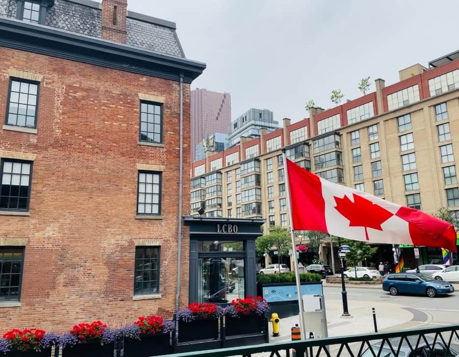 Front Street Toronto with a mix of historic and new building and a Canadian flag