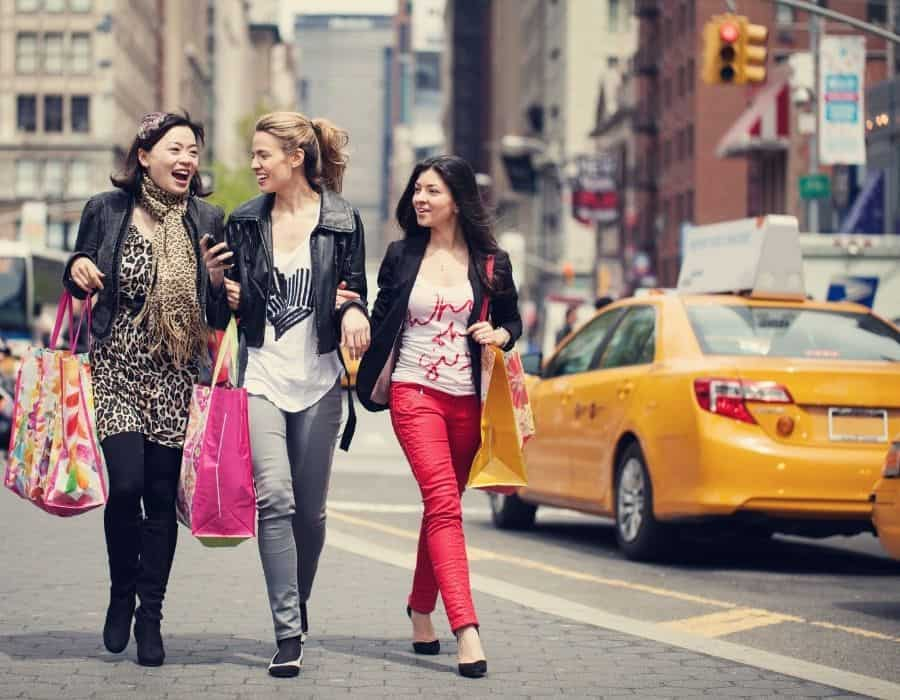 Women walk with shopping bags on a girls trip in New York City