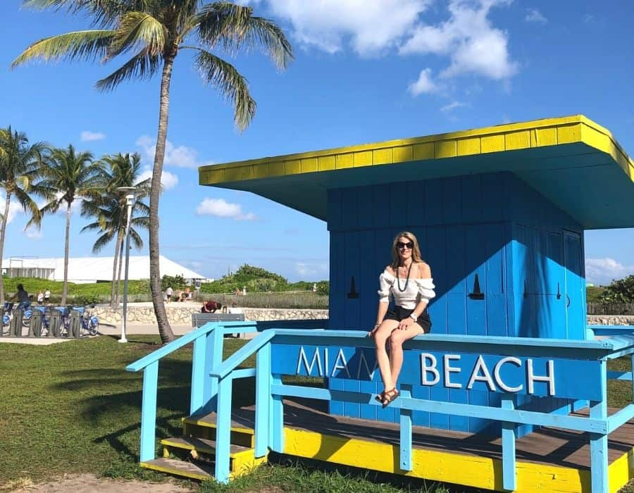 Susan Heinrich sits in a Miami Beach Lifeguard station with the beach beyond
