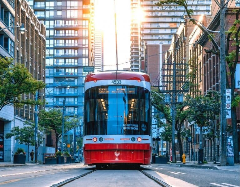 A red streetcar travels past highrise buildings on downtown Toronto