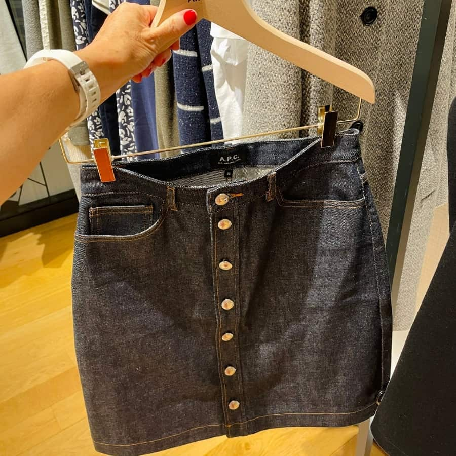 A woman's hand holds up a denim skirt by A.P.C. a French clothing brand