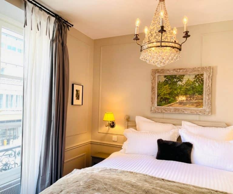A bed with a beautiful chandelier and French window in a holiday apartment in Paris w