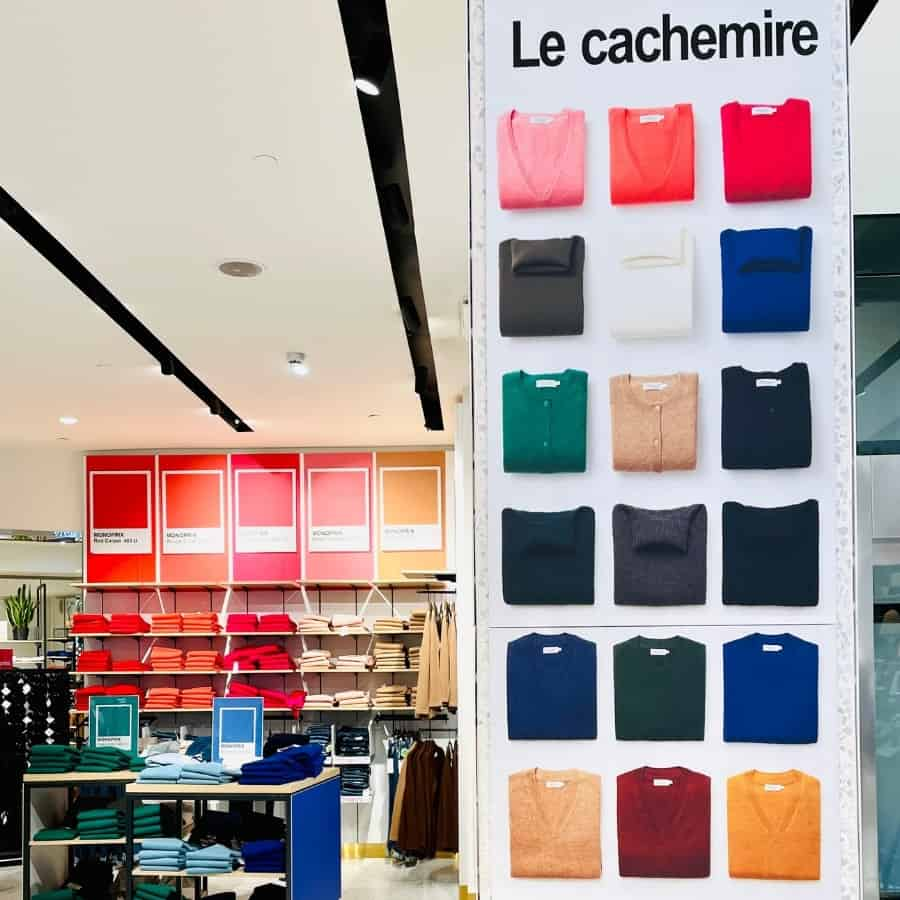 A wall of cashmere sweaters arranged by colour in the Monoprix Champs Elysees Paris store