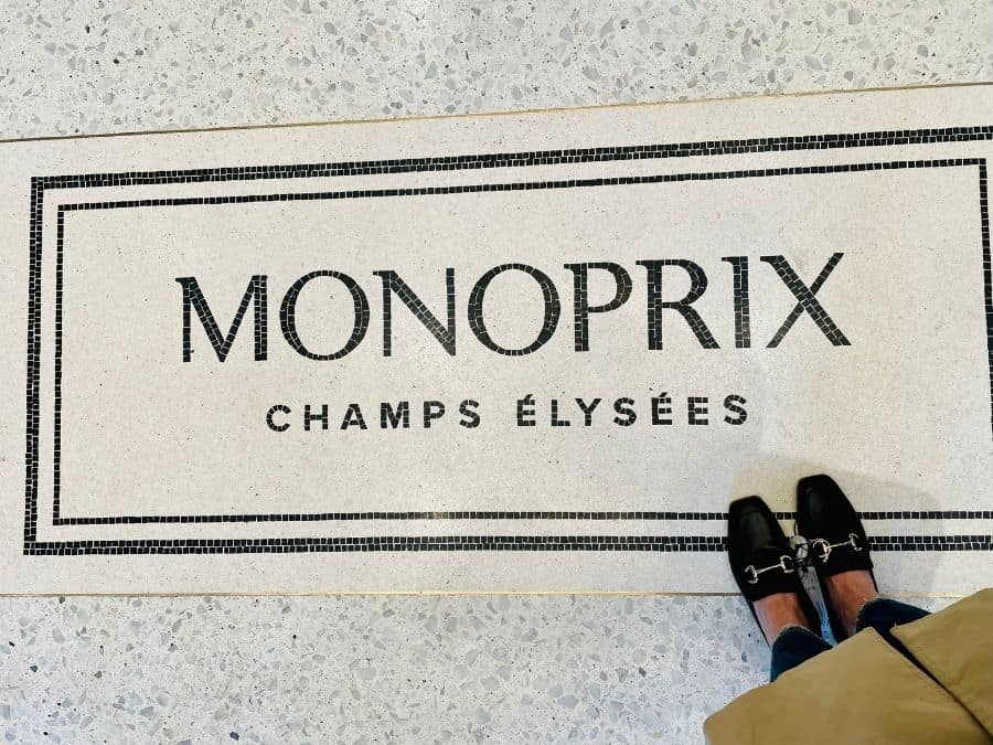 A woman's loafers stand on floor tiles with the words Monoprix Champs Elysées