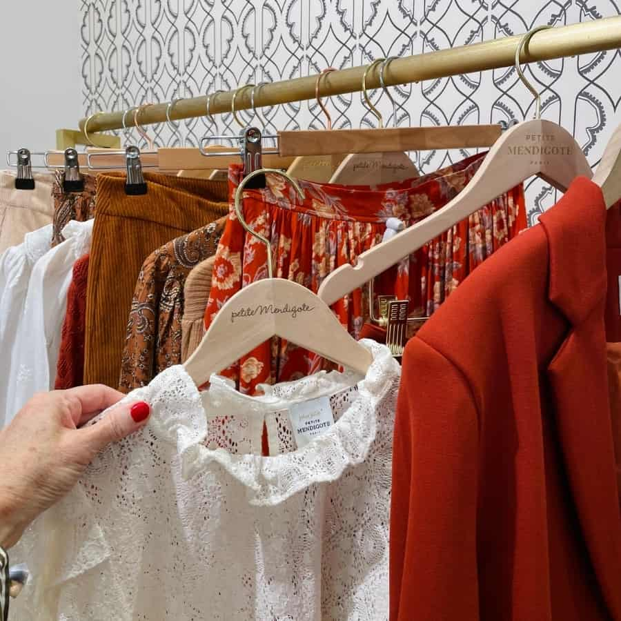 A woman's hand holds a white blouse next to blazers and skirts in fall colours at Petite Mendigot, an affordable French brand in Paris