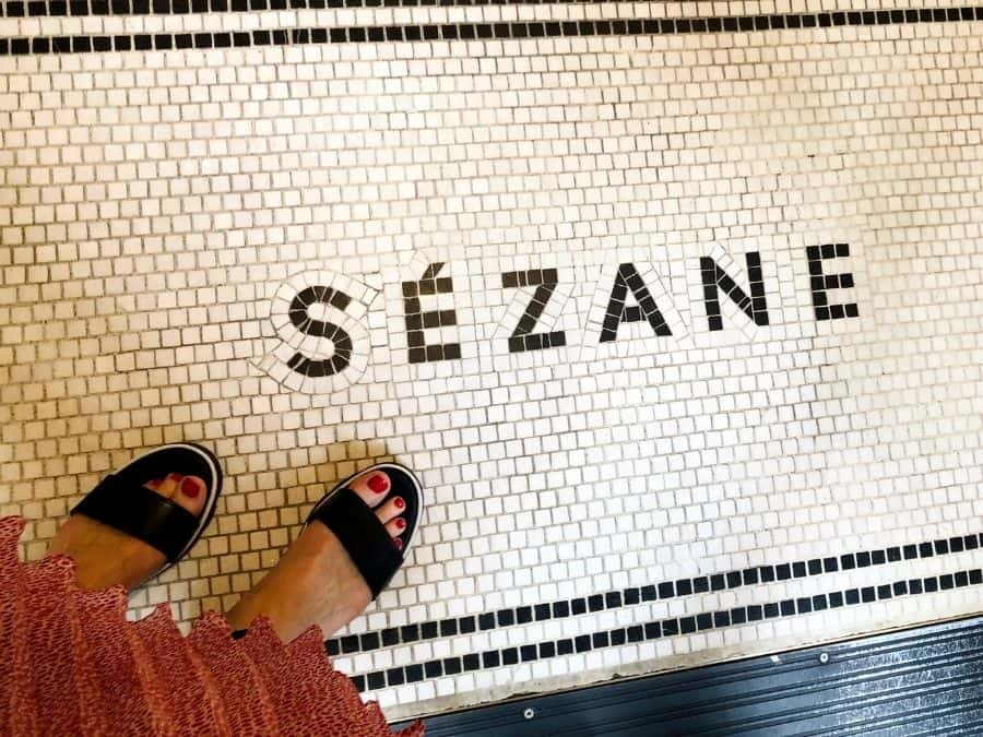 A woman's feet in dressy sandals stand on top of a floor tile sign that says Sézane