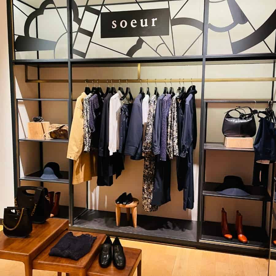 A rack of clothes by Soeur amidst stylish shelveswith shoes and bags. Soeur is an affordable French clothing brand from Paris