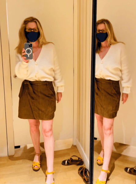 Susan Heinrich tries on a suede skirt and cream sweater at Sézane in Paris