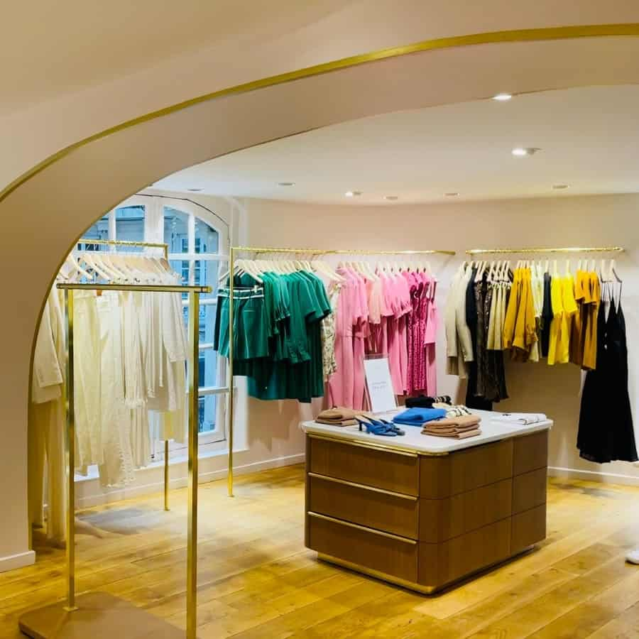 The Tara Jarmon Store in Paris with an arched ceiling and a rack of clothes hanging by colour